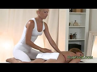 Blonde masseuse massages naked brunette